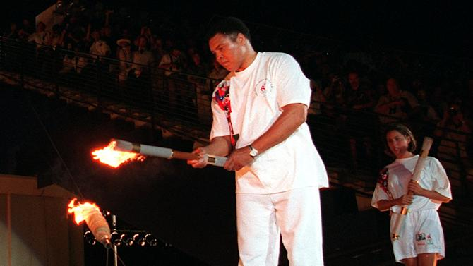 FILE - In this Friday, July 19, 1996 file photo, boxing legend Muhammed Ali lights the Olympic flame, as American swimmer Janet Evans looks on during the 1996 Summer Olympic Games opening ceremony in Atlanta. Only London Olympics Opening Ceremony director Danny Boyle and a few well-informed others will know for certain if British newspapers are wrong with their speculation that Ali could play a role on Friday night July 27, 2012 when the ceremony is held. (AP Photo/Michael Probst)