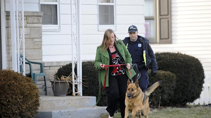 South Bend police remove a resident from her home near the scene of a plane crash near the South Bend Regional Airport Sunday March 17, 2013 in South Bend, Ind. The private jet apparently experiencing mechanical trouble crashed Sunday in a northern Indiana neighborhood, resulting in injuries and striking three homes, authorities and witnesses said.  (AP Photo/Joe Raymond)