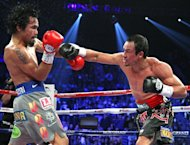 Manny Pacquiao (L) and Juan Manuel Marquez battle during their welterweight fight at the MGM Grand Garden in Las Vegas, Nevada. Marquez knocked out Pacquiao in the 6th round. Pacquiao says he welcomes another fight with Marquez, one that would put them into an elite class of boxing champions who have met five times in the ring
