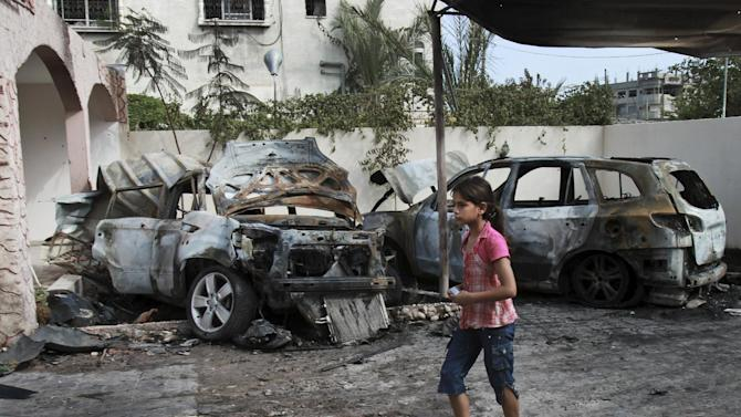 Fareda Abu Khosa, 12, walks past her father and brother's vehicles destroyed overnight in an Israeli air strike in Gaza City, Wednesday, June 20, 2012. Gaza Strip militants barraged southern Israel with rocket fire on Wednesday and Israel retaliated with multiple airstrikes, as a brief cease-fire crumbled shortly after it took effect. (AP Photo/Adel Hana)