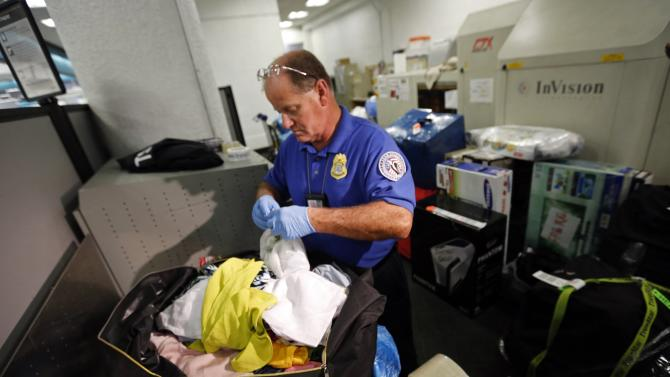 Transportation Security Administration baggage screener checks passengers' luggage at Miami International Airport in Miami