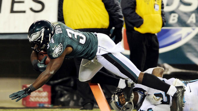 Philadelphia Eagles running back Bryce Brown (34) scores a touchdown as Carolina Panthers cornerback Josh Norman hangs on in the first half of an NFL football game, Monday, Nov. 26, 2012, in Philadelphia. (AP Photo/Michael Perez)