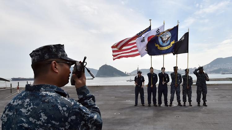 Crew members hold US and South Korean national flags on the on the flight deck of the USS George Washington at a South Korean naval port in Busan on July 11, 2014