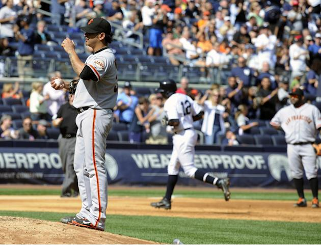 San Francisco Giants pitcher Guillermo Moscoso, left, and third baseman Pablo Sandoval, right, react as New York Yankees' Alfonso Soriano rounds the bases with a home run during the sixth inning of an