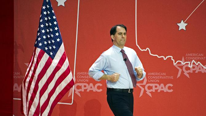 Wisconsin Gov. Scott Walker runs onstage to address the  Conservative Political Action Conference (CPAC) in National Harbor, Md., Thursday, Feb. 26, 2015. (AP Photo/Cliff Owen)