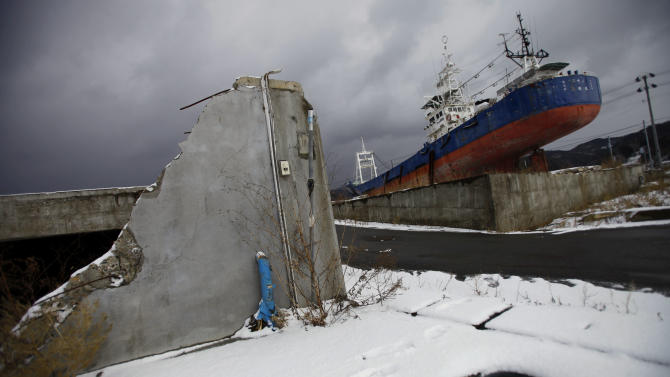 In this Sunday, Feb. 24, 2013 photo, a fishing boat washed ashore during the March 11, 2011 earthquake and tsunami sits in the devastated area in Kesennuma, Miyagi Prefecture. Japan's progress in rebuilding from the tsunami that thundered over coastal sea walls, sweeping entire communities away, is mainly measured in barren foundations and empty spaces. Clearing of forests on higher ground due to be leveled to make space for relocating survivors has barely begun. Japan will next week observes two years from the March 11, 2011 disasters which devastated in the northeastern Pacific coast of the country. (AP Photo/Junji Kurokawa)