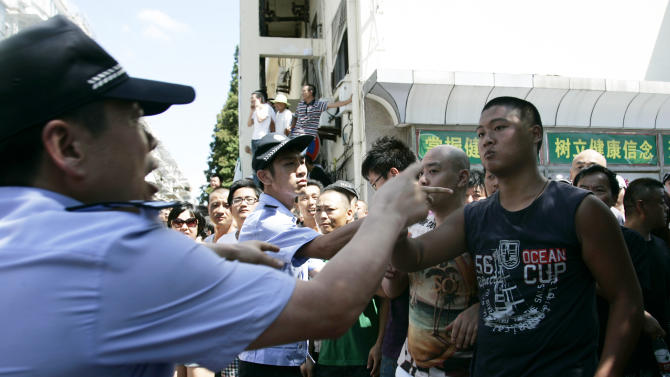 Protesters, right,  confront with police officers, left, near the local government office building Saturday July 28, 2012 in Qidong, Jiangsu Province,  China.  Authorities in eastern China dropped plans for a water-discharge project Saturday after thousands of protesters angry about pollution took to the streets, in the latest of many such confrontations in a country where three decades of rapid economic expansion have come at an environmental price. (AP Photo)