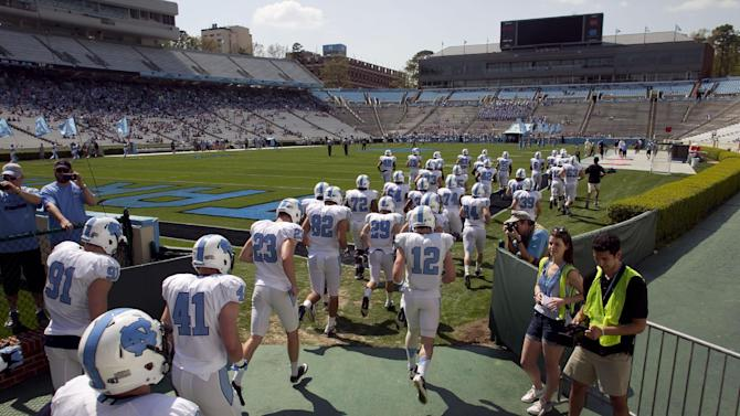 The white team enters Kenan Stadium for North Carolina's NCAA college football spring practice, Saturday, April 12, 2014, in Chapel Hill, N.C