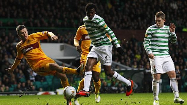 Celtic's Efe Ambrose(C) narrowly misses scoring a goal with his shot at goal as Motherwell's Simon Ramsden (L) challenges during their Scottish Premier League match