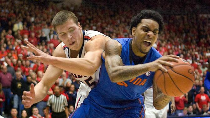 Florida's Mike Rosario (3) takes the ball away from Arizona's Kaleb Tarczewski (35) during the first half of an NCAA college basketball game at McKale Center in Tucson, Ariz., Saturday, Dec. 15, 2012. (AP Photo/Wily Low)