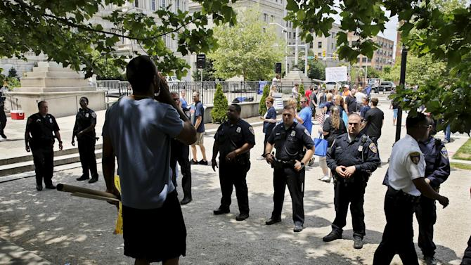 """Counter demonstrator jeers at police supporters as officers keep the two groups separated during a """"Blue Lives Matter"""" rally in support of the Baltimore police in Baltimore"""
