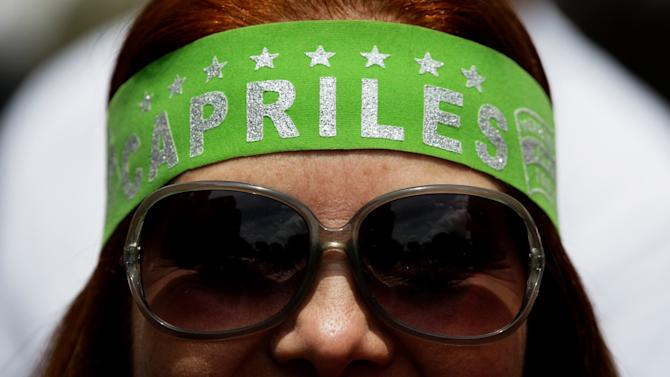 """An opposition protester wears a bandana that reads in Spanish """"Capriles"""" during the opposition May Day march in Caracas, Venezuela, Wednesday, May 1, 2013.  Venezuelans filled the streets of the capital Wednesday in rival marches by the opposition and the government less than a day after a brawl on the floor of congress injured several opposition lawmakers. (AP Photo/Fernando Llano)"""