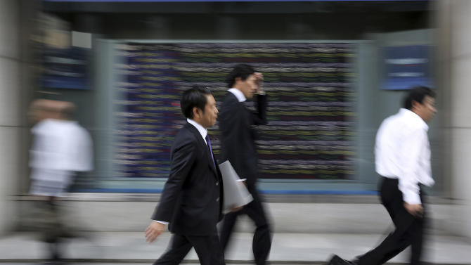 People walk past an electronic stock board of a securities firm in Tokyo Tuesday, May 26, 2015. European shares were mixed Tuesday as markets reopened after holidays on Monday, overshadowed by concerns over Greece's debt crisis. Asian shares gained as news from China of support for new infrastructure projects and a decision to slash tariffs on consumer goods spurred the Shanghai index to fresh highs. (AP Photo/Eugene Hoshiko)