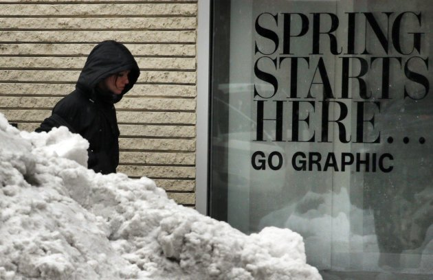 "A pedestrian walks past a pile of snow, and the words ""Spring Starts Here"" in a store window, during a late winter snow storm in Boston"