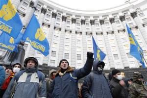 People gather in front of the Ukrainian cabinet of ministers building during a rally to support EU integration in Kiev