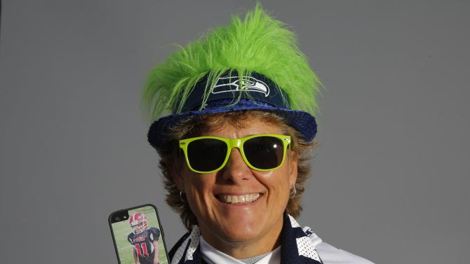 Seattle Seahawks fan Shelley Biggs, 52, poses for a portrait holding a cell phone with a photo of her nine-year-old son Brendan, in Phoenix