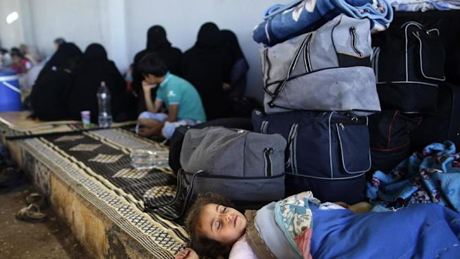 A Syrian girl, who fled her home with her family due to fighting between the Syrian army and the rebels, sleeps by her family's belongings, while she and others take refuge at the Bab Al-Salameh border crossing, in hopes of entering one of the refugee camps in Turkey, near the Syrian town of Azaz, Thursday, Aug. 23, 2012. Thousands of Syrians who have been displaced by the country's civil are struggling to find safe shelter while shelling and airstrikes by government forces continue. (AP Photo/Muhammed Muheisen)