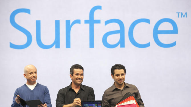 "Microsoft Surface design team members, from left, Steven Sinofsky, Mike Angiulo, and Panos Panay demonstrate ""Surface"", a new tablet computer at Hollywood's Milk Studios in Los Angeles Monday, June 18, 2012. The 9.3 millimeter thick tablet comes with a kickstand to hold it upright and keyboard that is part of the device's cover. It weighs under 1.5 pounds. (AP Photo/Damian Dovarganes)"