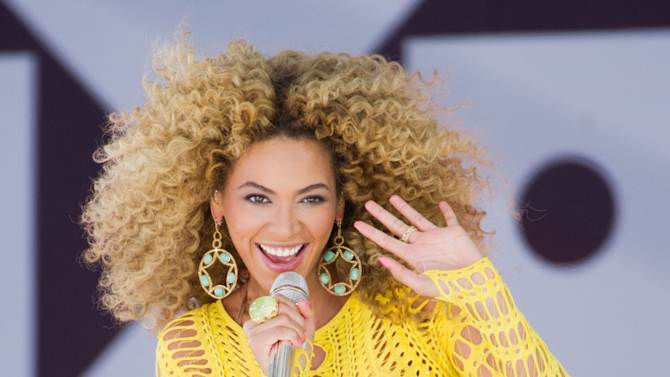 "FILE - In this July 1, 2011 file photo, Beyonce performs on ABC's ""Good Morning America"" in New York. Through a photo contest, 100 fans will join Beyonce onstage during the singer's halftime show performance at the 2013 Super Bowl on Feb. 3, 2013, at the Mercedes-Benz Superdome in New Orleans. (AP Photo/Charles Sykes, File)"