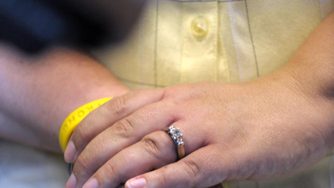 FILE - Jayne Rowse, left, and her partner April Deboer, both of Hazel Park, Mich., hold hands during a news conference Wednesday, June 26, 2013 in Detroit. Rowse and Deboer filed a lawsuit to try to overturn restrictions on adoption by same-sex partners in Michigan. Michigan's ban on gay marriage remains intact after a pair of U.S. Supreme Court decisions, though opponents may have picked up new arguments to challenge the state's voter-approved law, experts said Wednesday. (AP Photo/Detroit News, Todd McInturf)