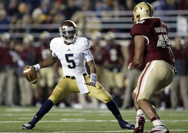 Notre Dame quarterback Everett Golson looks for an opening around Boston College Eagles defensive end Mehdi Abdesmad during the first half of an NCAA college football game in Boston on Saturday, Nov.