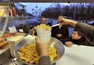 Josiane Devlaeminck serves fries at the Atomium 'fritkot' in Brussels. Across Belgium, there is a close-knit network of 'Fritkot', stalls, seen usually on town squares or busy streets, often with long patient queues waiting