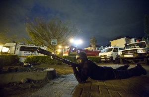 An armed police officer takes cover during a bout of …