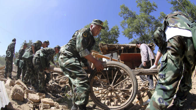 Chinese paramilitary policemen helps residents remove belongings from quake damaged houses in Lalu village of Hetuo township in Minxian in northwest China's Gansu province Monday July 22, 2013. A strong earthquake that shook an arid, hilly farming area in northwest China sparked landslides and destroyed or damaged thousands of brick-and-mud homes Monday, killing at least 75 people and injuring more than 400, the government said. (AP Photo) CHINA OUT
