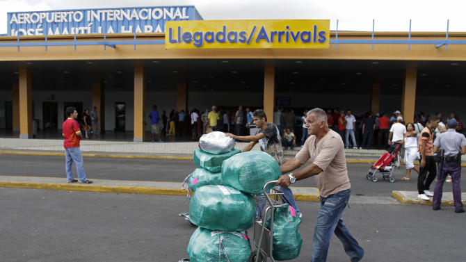 Juan, a Cuban-American man who did not want to give his last name, front, arrives with packages after getting off a flight from the U.S. as his brother, who lives in Cuba, behind, helps him with other packages at the Jose Marti International Airport in Havana, Cuba, Monday, Sept. 3, 2012.  A steep hike in customs duties has taken effect in Cuba, catching some air travelers unaware and leaving others irate at the new fees. (AP Photo/Franklin Reyes)