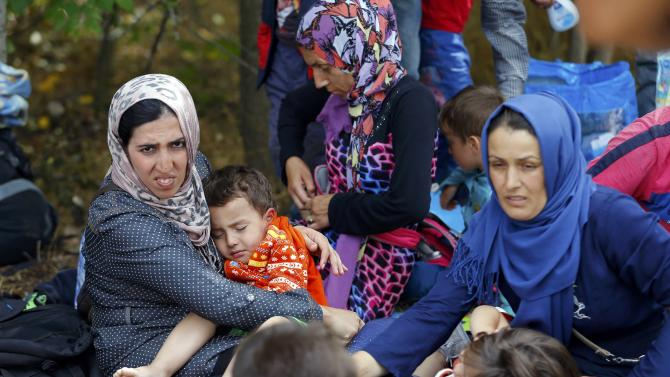 Migrant women take care of the children on the side of a road after crossing the border illegally from Serbia, near Asotthalom