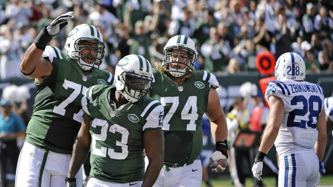 New York Jets running back Shonn Greene (23) celebrates a touchdown with teammtes Austin Howard (77) and Nick Mangold (74) as Indianapolis Colts strong safety Tom Zbikowski (28) walks away during the first half of an NFL football game Sunday, Oct. 14, 2012 in East Rutherford, N.J. (AP Photo/Bill Kostroun)