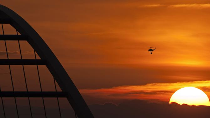 A helicopter transports sandbags to a flooded area by river Elbe besides a bridge during the sunset near Fischbeck, central Germany, Monday, June 10, 2013. Weeks of heavy rain this spring have sent the Elbe, the Danube and other rivers such as the Vltava and the Saale overflowing their banks, causing extensive damage in central and southern Germany, the Czech Republic, Austria, Slovakia and Hungary. (AP Photo/Jens Meyer)