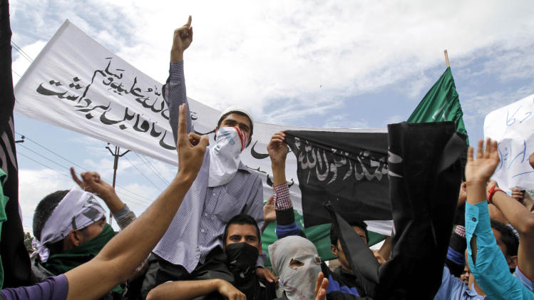 "Kashmiri Muslims shout slogans against the U.S. during a protest in Srinagar, India, Tuesday, Sept. 18, 2012. The protest was held against an anti-Islam film called ""Innocence of Muslims"" that ridicules Islam's Prophet Muhammad. Banner reads ""Muslims can sacrifice their precious lives for Prophet Muhammad."" (AP Photo/Mukhtar Khan)"