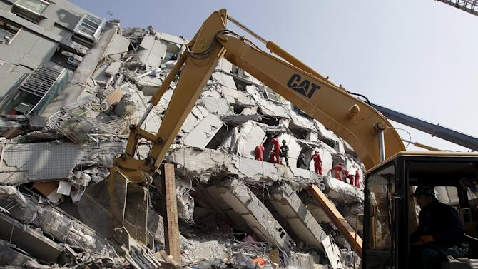 Rescue personnel work at the site where a 17-storey apartment building collapsed in an earthquake in Tainan
