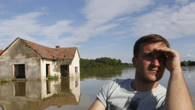 A Bosnian man searches for people and animals after flooding in the village of Vojskova near the Bosnian town of Bosanski Samac, flooded by the river Sava, 200 km's north of the Bosnian capital of Sarajevo, on Monday, May 19, 2014. Tens of thousands evacuated in Serbia and Bosnia during worst floods in a century.(AP Photo/ Amel Emric)