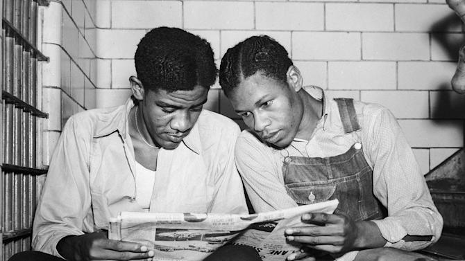 FILE - In this July 16, 1937 file photo, Charlie Weems, left, and Clarence Norris, Scottsboro case defendants, read a newspaper in jail Decatur, Ala. after Norris was found guilty for a third time by a jury which specified the death penalty. Weems was to be tried a week later. Nine black teenagers known as the Scottsboro Boys were convicted by all-white juries of raping two white women on a train in Alabama in 1931. All but the youngest were sentenced to death, even though one of the women recanted her story. All eventually got out of prison, but only one received a pardon before he died. (AP Photo)