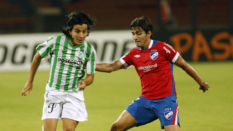 Cardenas of Atletico Nacional and Calzada of Nacional fight for the ball during their Copa Libertadores soccer match in Medellin