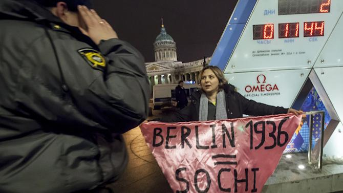 """A gay rights activist holds a banner in front of a large clock showing the number of days left until the start of the Olympic games as a police officer approaches, left, in St. Petersburg, Russia, Wednesday, Feb. 5, 2014. Russian gay rights activists protested the upcoming Olympic Games in Sochi. Two activists unfurled banners reading """"Berlin 1936 = Sochi 2014,"""" referring to the Olympic Games that were held in the capital of Nazi Germany. One-man pickets are legal in Russia and the two activists holding signs were spaced far enough apart that neither was arrested. (AP Photo/Elena Ignatyeva)"""