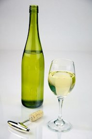 A glass of white wine stands next to a green-hued bottle.
