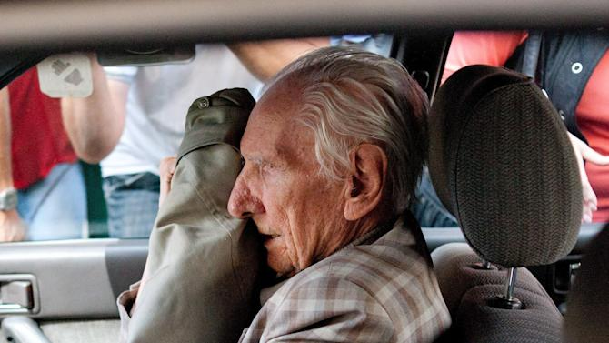 FILE This Wednesday, July 18, 2012 file photo shows alleged Hungarian war criminal Laszlo Csatary covering his face in a car as he leaves the Budapest Prosecutor's Office after he was questioned by detectives on charges of war crimes during WWII and prosecutors ordered his house arrest in Budapest, Hungary. Csatary, a former police officer indicted in June 2013 by Hungarian authorities for abusing Jews and contributing to their deportation to Nazi death camps during World War II, has died. He was 98. Csatary died Saturday Aug. 11, 2013 of pneumonia in a Budapest hospital, said his lawyer, Gabor Horvath B. (AP Photo/MTI, Bea Kallos, File)