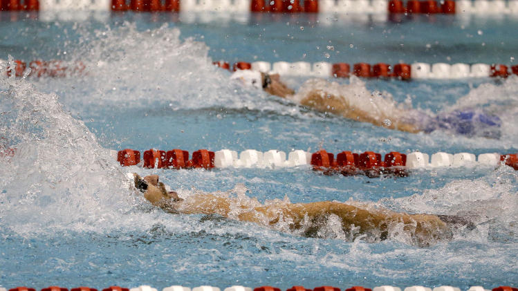 Michael Phelps, left, leads Ryan Lochte, right, in the final lap to win the men's 100-meter backstroke at the Bulldog Grand Slam swim meet at the University of Georgia, Saturday, July 12, 2014, in Athens, Ga. Lochte took second place in the event. (AP Photo/David Goldman)