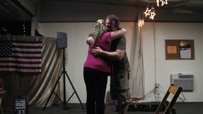 """In this Thursday, June 7, 2012 photo, Jason Moon, right, a veteran and singer-songwriter, gets a hug from Claudia Zuniga after his concert in Glendale, Calif. When Moon, who served in the Army in the Iraq War, plays his service-inspired music at concerts around the country, he sings of """"things I've seen I won't forget,"""" about sacrifices that many warriors bear. (AP Photo/Jae C. Hong)"""