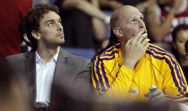 Los Angeles Lakers forward Pau Gasol, left, of Spain, sits on the bench with Lakers center Chris Kaman, checking out the scoreboard in an NBA basketball preseason game against the Golden State Warrior