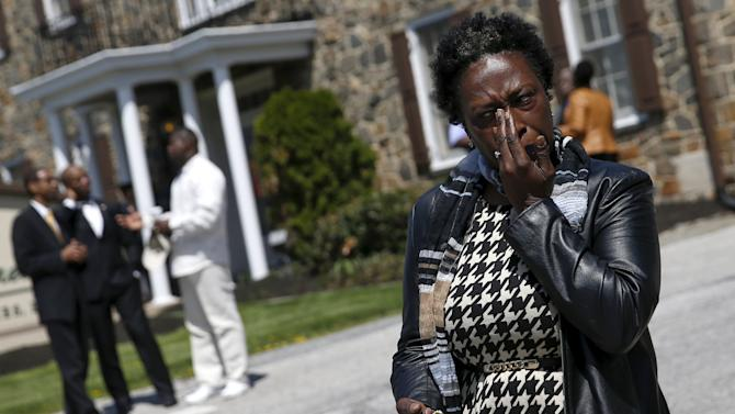 Frances Hardy wipes her face after paying her respects for Freddie Gray, who died following an arrest in Baltimore, at his wake in Baltimore, Maryland