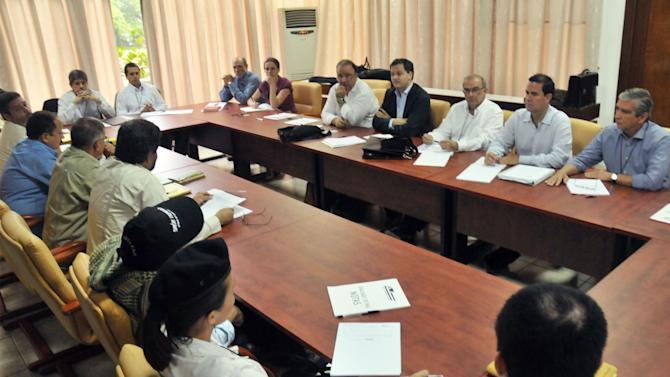 FILE - In this Nov. 19, 2012 file picture released by Colombia's government's delegation, representatives from the government's negotiation team, right, sit across the table from representatives of the Revolutionary Armed Forces of Colombia, or FARC, negotiation team on the first day of peace talks in Havana, Cuba. While the angry rhetoric and bombs continue to fly back home, Colombian rebels and government negotiators in peace talks in the Cuban capital describe an increasingly collegial atmosphere and growing trust between otherwise mortal enemies. (AP Photo/Omar Nieto Remolina, Government of Colombia, File)