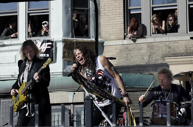 Aerosmith members, from left, Tom Hamilton, Steven Tyler and Joey Kramer perform a free concert Monday, Nov. 5, 2012 in Boston&#39;s Allston neighborhood as fans watch from the apartment building which was their home in the early 1970&#39;s. (AP Photo/Elise Amendola)