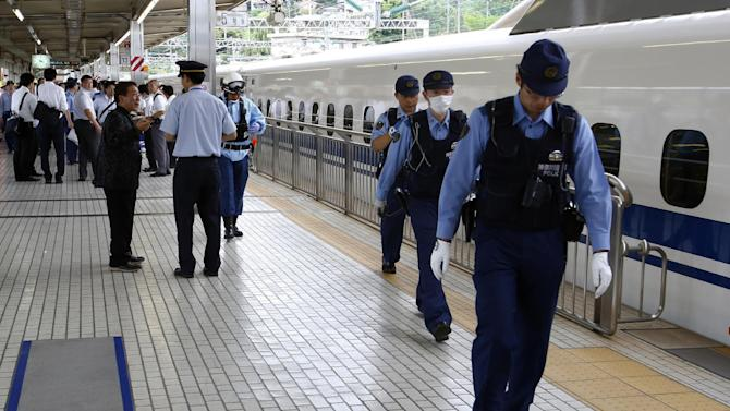 FILE- In this June 30, 2015 file photo, a passenger, left, talks with a station employee on a platform after getting off a high-speed bullet train where a man set himself of fire, at Odawara station in Odawara, west of Tokyo. A fatal fire on Japan's bullet train, started by a man who self-immolated this week, has revealed surprising blind spots in a system renowned for its speed, punctuality and safety record. Experts say it was a wakeup call to something more disastrous, potentially terrorist attacks, and it's time to step up risk management ahead of the G-7 summit in Japan next year and the 2020 Tokyo Olympics. (AP Photo/Shizuo Kambayashi, File)