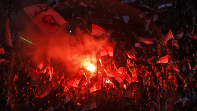 "Opponents of Egypt's Islamist President Mohammed Morsi celebrate as they light flares and wave national flags and his picture with Arabic reads, ""leave"", in Tahrir Square in Cairo, Egypt, Wednesday, July 3, 2013. Army troops backed by armor and including commandos have deployed across much of the Egyptian capital, near protest sites and at key facilities and major intersections. The deployment is part of a bid by the military to tighten its control of key institutions Wednesday, slapping a travel ban on embattled president Mohammed Morsi and top allies in preparation for an almost certain push to remove the Islamist president with the expiration of an afternoon deadline. (AP Photo/Amr Nabil)"