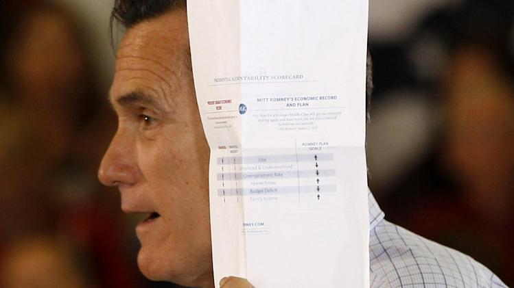 "Republican presidential candidate, former Massachusetts Gov. Mitt Romney holds up a ""presidential accountability scorecard"" comparing himself to President Barack Obama, as he campaigns at the Jefferson County Fairgrounds in Golden, Colo., Thursday, Aug. 2, 2012. (AP Photo/Charles Dharapak)"