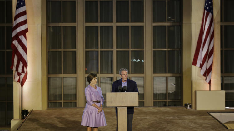 Former president George W. Bush, right, with former first lady Laura Bush, addresses the audience during the lighting of Freedom Hall ceremony at the George W. Bush Presidential Center Thursday, April 25, 2013, in Dallas. (AP Photo/David J. Phillip) (AP Photo/David J. Phillip)